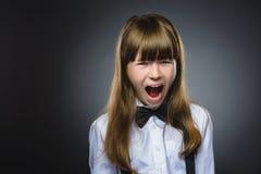 Close-upportret van knap meisje met verbaasde uitdrukking terwijl status tegen grijze achtergrond Royalty-vrije Stock Foto