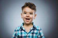 Close-upportret van knappe jongen met verbaasde uitdrukking op grijze achtergrond royalty-vrije stock afbeelding