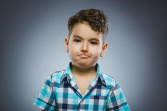 Close-upportret van knappe jongen met verbaasde uitdrukking op grijze achtergrond stock fotografie