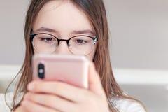 Close-upportret van leuk ernstig tween meisje die in glazen smartphone in haar handen bekijken stock fotografie