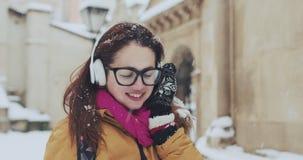 Close-upportret van leuk glimlachend jong meisje die over het sneeuwweer zijn weggegaan, die aan muziek met haar radio luisteren stock video