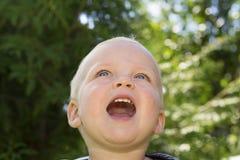 Close-upportret van leuke glimlachende één jaarpeuter tegen groene aardachtergrond aanbiddelijke babyjongen die omhooggaand kijke royalty-vrije stock foto
