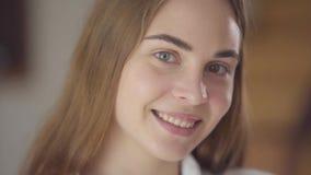 Close-upportret van leuke jonge glimlachende vrouw die met verschillende gekleurde ogen camera in de ochtend bekijken gelukkig stock video