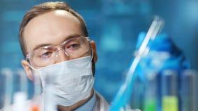 Close-upportret van mannelijke chemic arts die beschermend masker dragen die aan vaccin van virus werken stock video