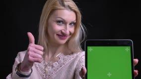 Close-upportret van midden oud Kaukasisch wijfje gebruikend de tablet en tonend het groene chromascherm aan camera stock videobeelden