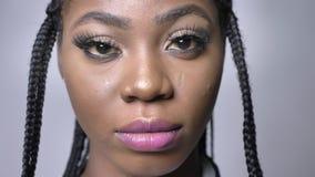 Close-upportret van mooi Afrikaans meisje die camera met trots en vertrouwen op grijze folie bekijken stock video