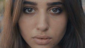 Close-upportret van mooi jong vrouwen donkerbruin model die de camera op een achtergrond van de stadsstraat bekijken Meisje met stock videobeelden
