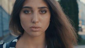 Close-upportret van mooi jong vrouwen donkerbruin model die de camera op een achtergrond van de stadsstraat bekijken Meisje met stock footage