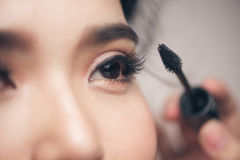 Close-upportret van mooi meisje wat betreft zwarte mascara hij Royalty-vrije Stock Foto