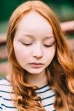 Close-upportret van mooi nadenkend meisje met lang krullend rood haar in de zomerpark Openluchtportret van een roodharige tiener stock foto's