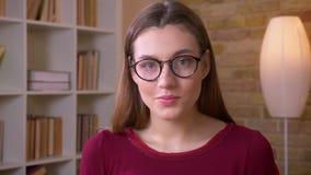 Close-upportret van mooie donkerbruine langharige vrouwelijke student in de horloges van oogglazen calmly en vast in camera stock video