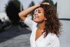 Close-upportret van mooie glimlachende jonge vrouw met lang donkerbruin haar die op de wind vliegen royalty-vrije stock foto