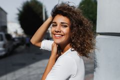 Close-upportret van mooie glimlachende jonge vrouw met lang donkerbruin haar die op de wind vliegen stock foto