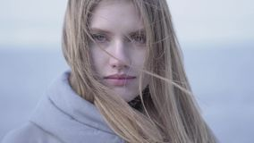 Close-upportret van mooie jonge blonde vrouw die met lang haar en blauwe ogen in de camera kijken Aantrekkelijke vrouw van stock videobeelden