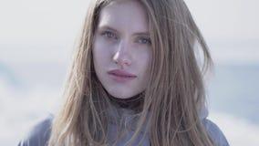 Close-upportret van mooie jonge blonde vrouw die met lang haar en blauwe ogen in de camera kijken Aantrekkelijke vrouw van stock video
