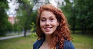 Close-upportret van mooie jonge dame die bij camera in park in de zomer glimlachen stock footage