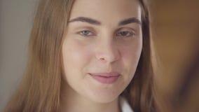 Close-upportret van mooie jonge glimlachende vrouw die met verschillende gekleurde ogen camera in de ochtend bekijken gelukkig stock videobeelden