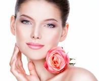 Close-upportret van mooie jonge vrouw met bloem dichtbij gezicht Royalty-vrije Stock Afbeeldingen