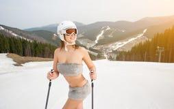 Close-upportret van naakte vrouwelijke skiër met helm Het meisje glimlacht en geniet van de de lentezon op de sneeuwhelling stock foto