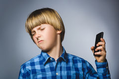 Close-upportret van ongerust gemaakte beklemtoonde jongen met mobiele gaande irritatie op grijze achtergrond royalty-vrije stock foto's