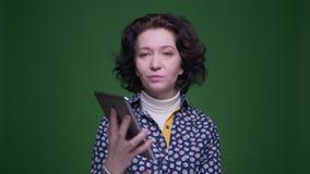 Close-upportret van oud Kaukasisch donkerbruin wijfje die die de tablet met achtergrond gebruiken op groen wordt geïsoleerd stock videobeelden