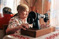 Close-upportret van oude vrouw die naaimachine, 70 jaar met behulp van naaisters die thuis werken stock foto