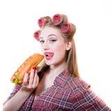 Close-upportret van pinup mooie blonde jonge vrouw met blauwe ogen die pret in krulspelden hebben die hotdog op een witte achterg Royalty-vrije Stock Afbeelding