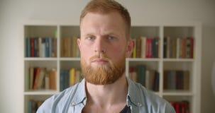 Close-upportret van roodharige gebaarde Kaukasische mannelijke student die camera in de bibliotheek bekijken stock videobeelden