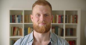 Close-upportret van roodharige gebaarde Kaukasische mannelijke student die gelukkig het bekijken camera in de bibliotheek glimlac stock video