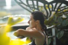 Close-upportret van sexy slank wijfje in zwembad tussen groene struiken royalty-vrije stock foto