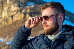 Close-upportret van Strenge en ernstige Hipster-reiziger met een baard in zonnebril in de aard Stock Foto