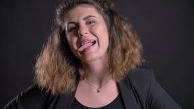 Close-upportret van te zware Kaukasische vrouw die gelukkig vreemde gezichten maken lettend op in camera op zwarte achtergrond stock videobeelden