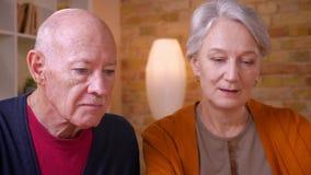 Close-upportret van twee hogere grijs-haired Kaukasische echtgenoten die in videochat op laptop spreken die blij in bureau zijn stock footage