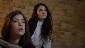 Close-upportret van twee jonge Kaukasische meisjes die in woonkamer zitten en op TV met groot vermaak letten stock videobeelden