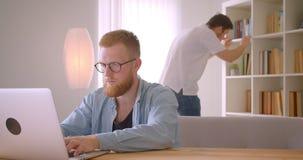 Close-upportret van twee succesvolle Kaukasische zakenlieden die in de bibliotheek samenwerken Men typt op laptop stock video