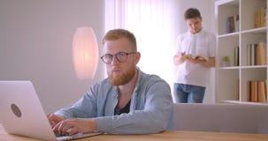 Close-upportret van twee volwassen Kaukasische zakenlieden die in de bibliotheek samenwerken Men typt op laptop terwijl stock video