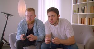 Close-upportret van twee volwassen knappe aantrekkelijke mensen die videospelletjes spelen die op de laag binnen zitten stock video
