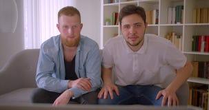 Close-upportret van twee volwassen knappe Kaukasische mensen die op sporten op de ontspannende zitting van TV op de laag binnen l stock video