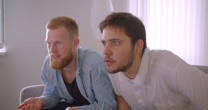 Close-upportret van twee volwassen knappe Kaukasische mensen die op sporten op TV letten die boze en gefrustreerde zitting worden stock videobeelden