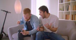 Close-upportret van twee volwassen knappe Kaukasische mensen die videospelletjes spelen die op de bank binnen zitten Winnaar plag stock video