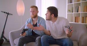 Close-upportret van twee volwassen knappe Kaukasische mensen die videospelletjes voor pretzitting binnen spelen op de laag stock video
