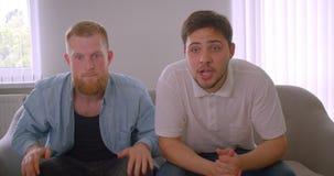 Close-upportret van twee volwassen knappe Kaukasische mensen die voetbal op spel op de TV-zitting op de laag binnen letten stock video