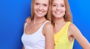 Close-upportret van twee vrouwen glimlachen geïsoleerd op blauwe achtergrond Royalty-vrije Stock Foto