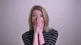 Close-upportret van volwassen aantrekkelijk blonde Kaukasisch wijfje die met opwinding glimlachen die camera met achtergrond beki stock videobeelden