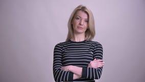 Close-upportret van volwassen aantrekkelijk blonde Kaukasisch wijfje die over borst hebben gekruist die camera met vertrouwen bek stock videobeelden