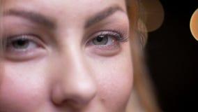 Close-upportret van volwassen aantrekkelijk blonde Kaukasisch wijfje die vooruit openend en sluitend haar ogen met bokeh kijken stock video