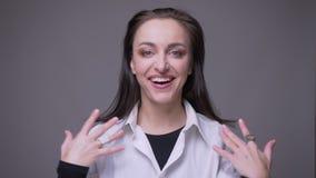 Close-upportret van volwassen aantrekkelijk Kaukasisch en het verraste wijfje die bekijken camera met achtergrond worden opgewekt stock video
