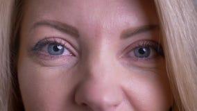Close-upportret van volwassen aantrekkelijk Kaukasisch vrouwelijk gezicht met ogen die camera met blije gelaatsuitdrukking bekijk stock footage