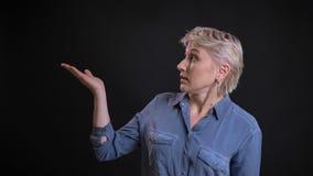 Close-upportret van volwassen aantrekkelijk Kaukasisch wijfje die een presentatie die met haar hand aantonen aan de kant richten stock foto
