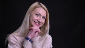 Close-upportret van volwassen aantrekkelijk Kaukasisch wijfje die en glimlachend gelukkig voor de camera worden opgewekt stock videobeelden